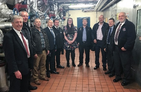 A photograph of group from the Association of University Engineers in the engine and boiler room of Dundee University's CHP plant