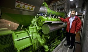 A view of a green Jenbacher gas engine with man at Edinburgh Universities CHP facility
